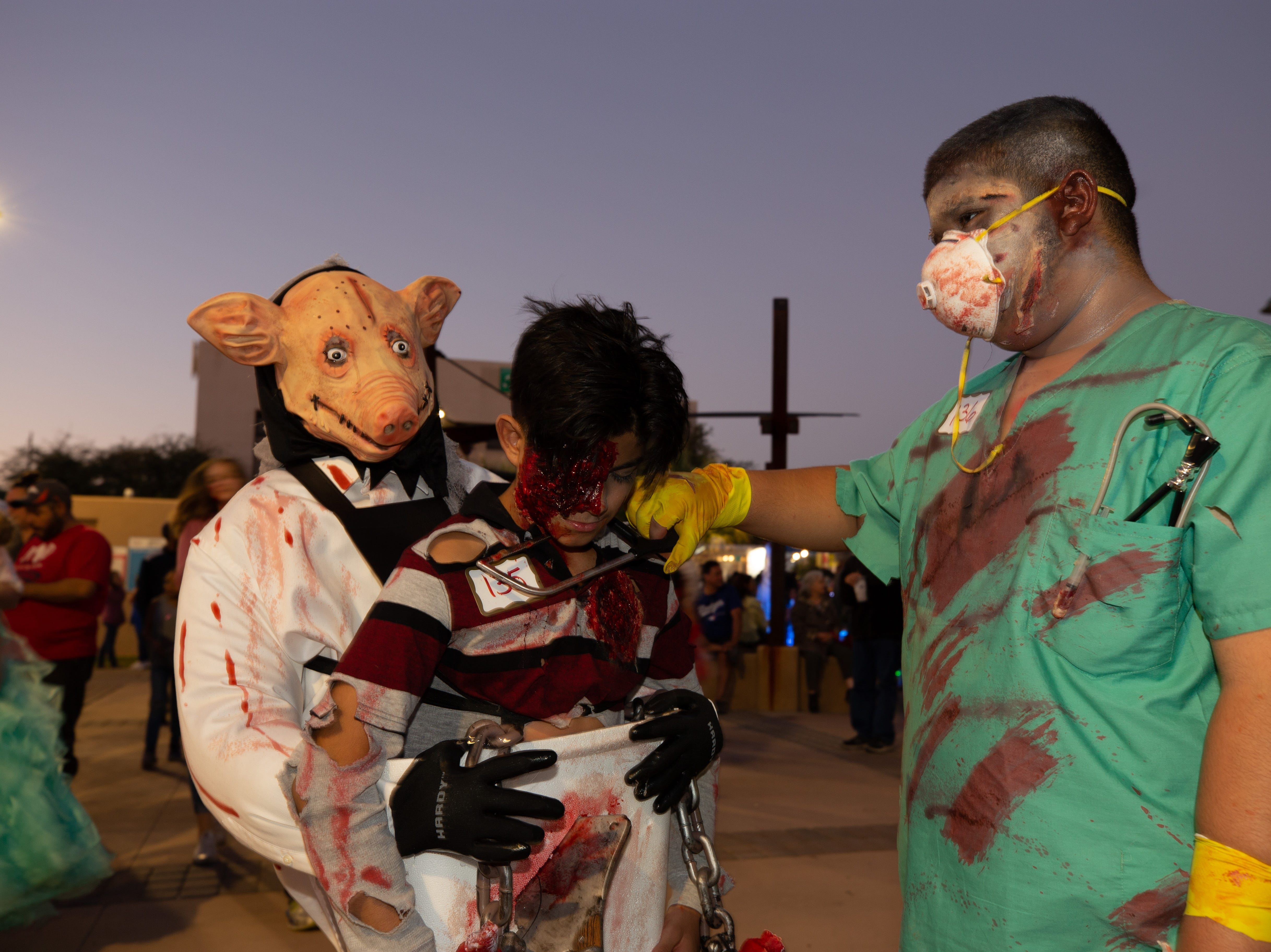 Doctor Death gets ready to take another victim during the Zombie Walk. Pictured left to right is the Creepy Pig Zavier Udero, 12; and Josiah Bazan, 13. The 2018 Zombie Walk held on Saturday, Oct. 27, 2018.