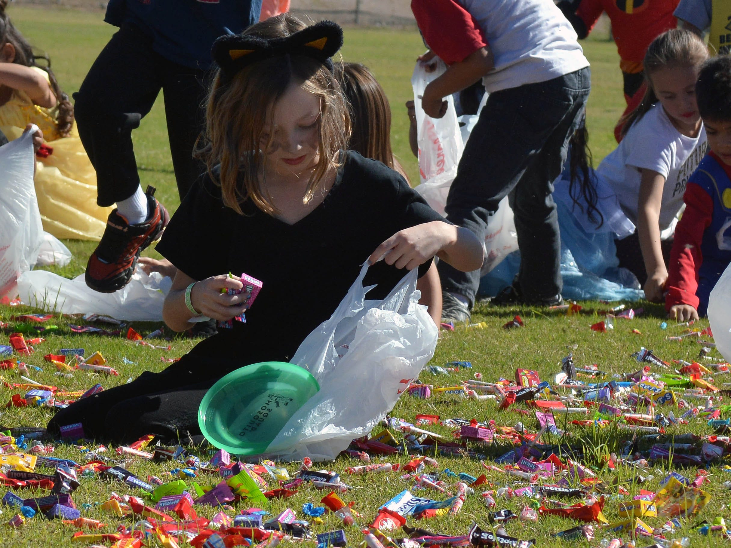 Rebyl Brewer, 6, fills her bag after finding a nice pile of candy during the 14th annual Great Pumpkin Candy Drop, held Sunday, Oct, 28 at Maag Park.
