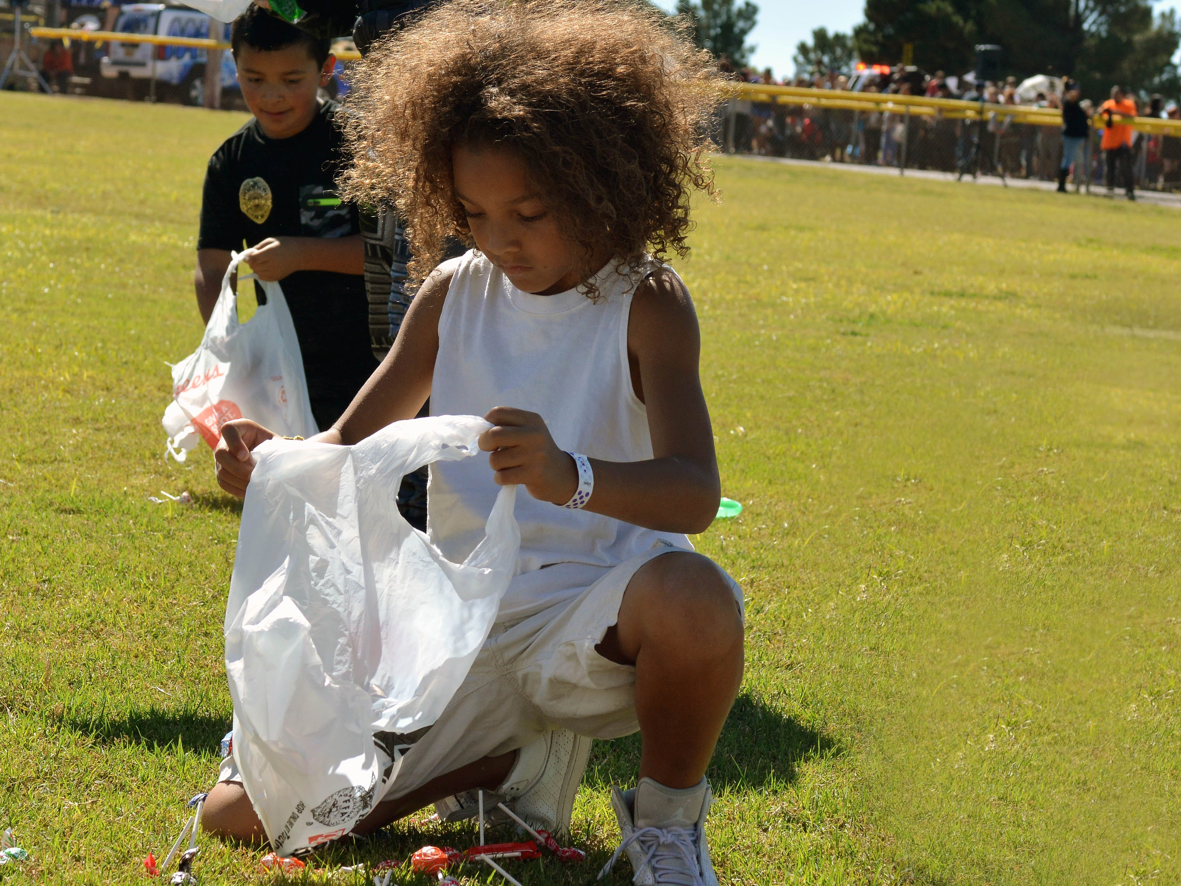 Eziah O'Kelley, 8, gathers candy during the 14th annual Great Pumpkin Candy Drop, held Sunday, Oct, 28 at Maag Park.