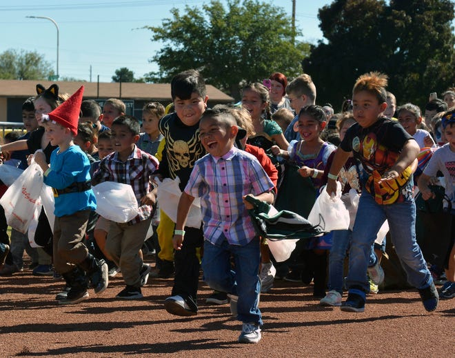 Children make the mad dash to the candy dropped during the 14th annual Great Pumpkin Candy Drop, held Sunday, Oct, 28 at Maag Park.