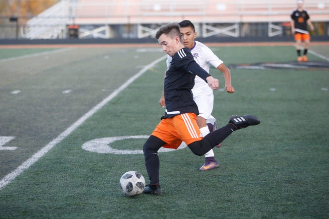 Aztec's Carson Collins launches the ball downfield against Kirtland Central's Anesio Villegas during Thursday's District 1-4A match at Fred Cook Stadium in Aztec. Visit daily-times.com to see the latest area soccer photo galleries.