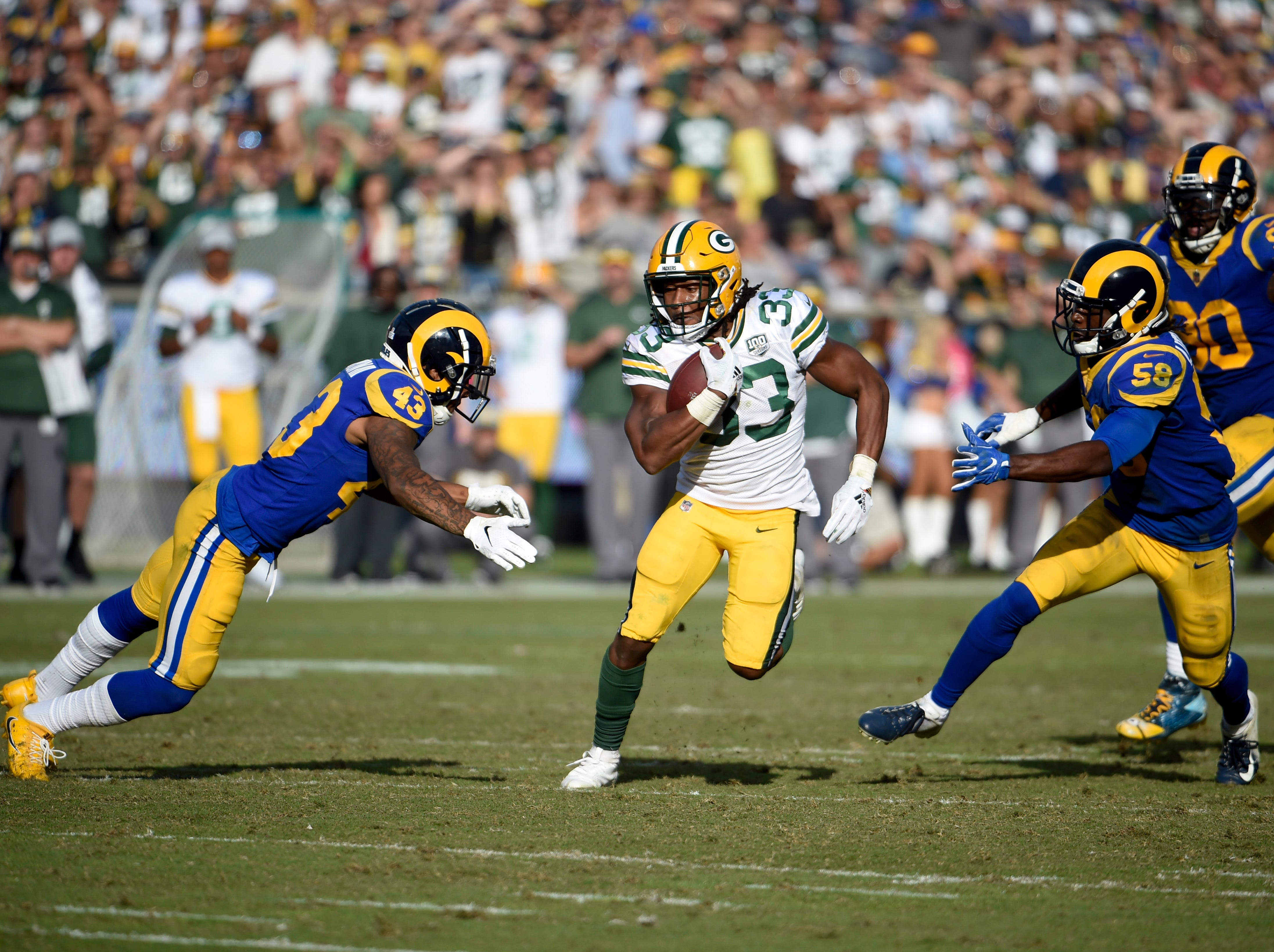 Green Bay Packers running back Aaron Jones (33) gets past Los Angeles Rams strong safety John Johnson on his way to scoring a touchdown during the second half of an NFL football game, Sunday, Oct. 28, 2018, in Los Angeles. (AP Photo/Denis Poroy)