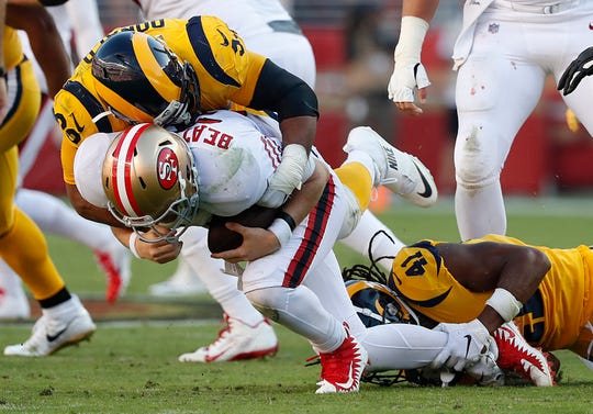 Los Angeles Rams defensive tackle Aaron Donald, top, sacks San Francisco 49ers quarterback C.J. Beathard during the second half of an NFL football game in Santa Clara on Oct. 21, 2018.