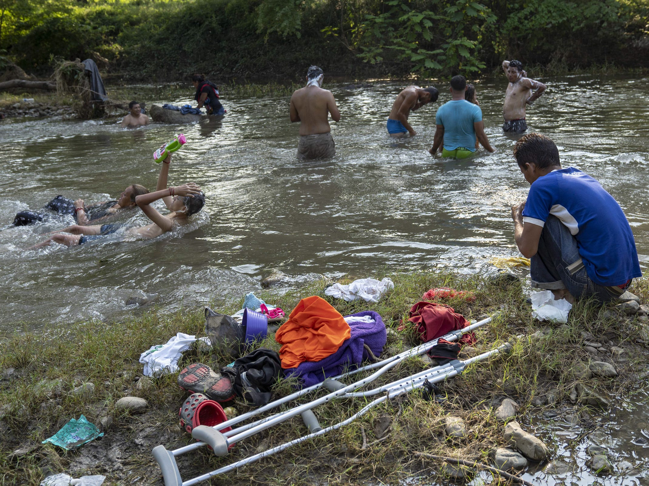 Bathing in the river offers a little relief from a day of walking in the oppressive heat for some of the thousands of migrants in the caravan on Oct. 27.