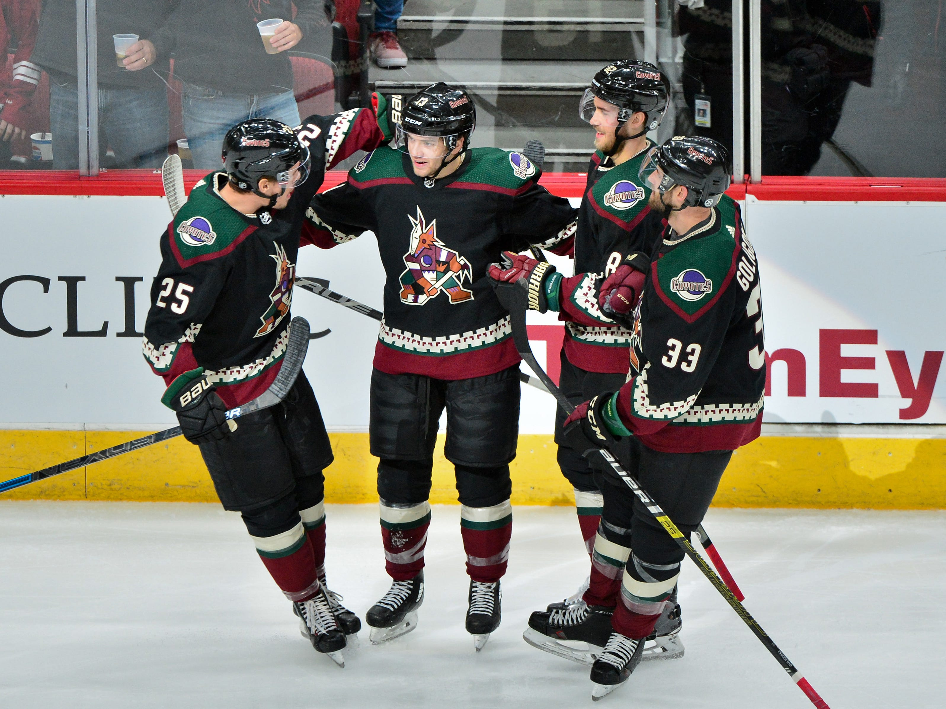 Oct 27, 2018; Glendale, AZ, USA; Arizona Coyotes center Vinnie Hinostroza (13) celebrates with center Nick Cousins (25), defenseman Alex Goligoski (33) and defenseman Jordan Oesterle (82) after scoring a goal in the second period against the Tampa Bay Lightning at Gila River Arena. Mandatory Credit: Matt Kartozian-USA TODAY Sports