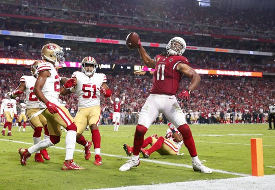 Arizona Cardinals wide receiver Larry Fitzgerald (11) spikes the football after a two-point conversion against the San Francisco 49ers In the fourth quarter during NFL action against the San Francisco 49ers on Oct. 28 at State Farm Stadium.