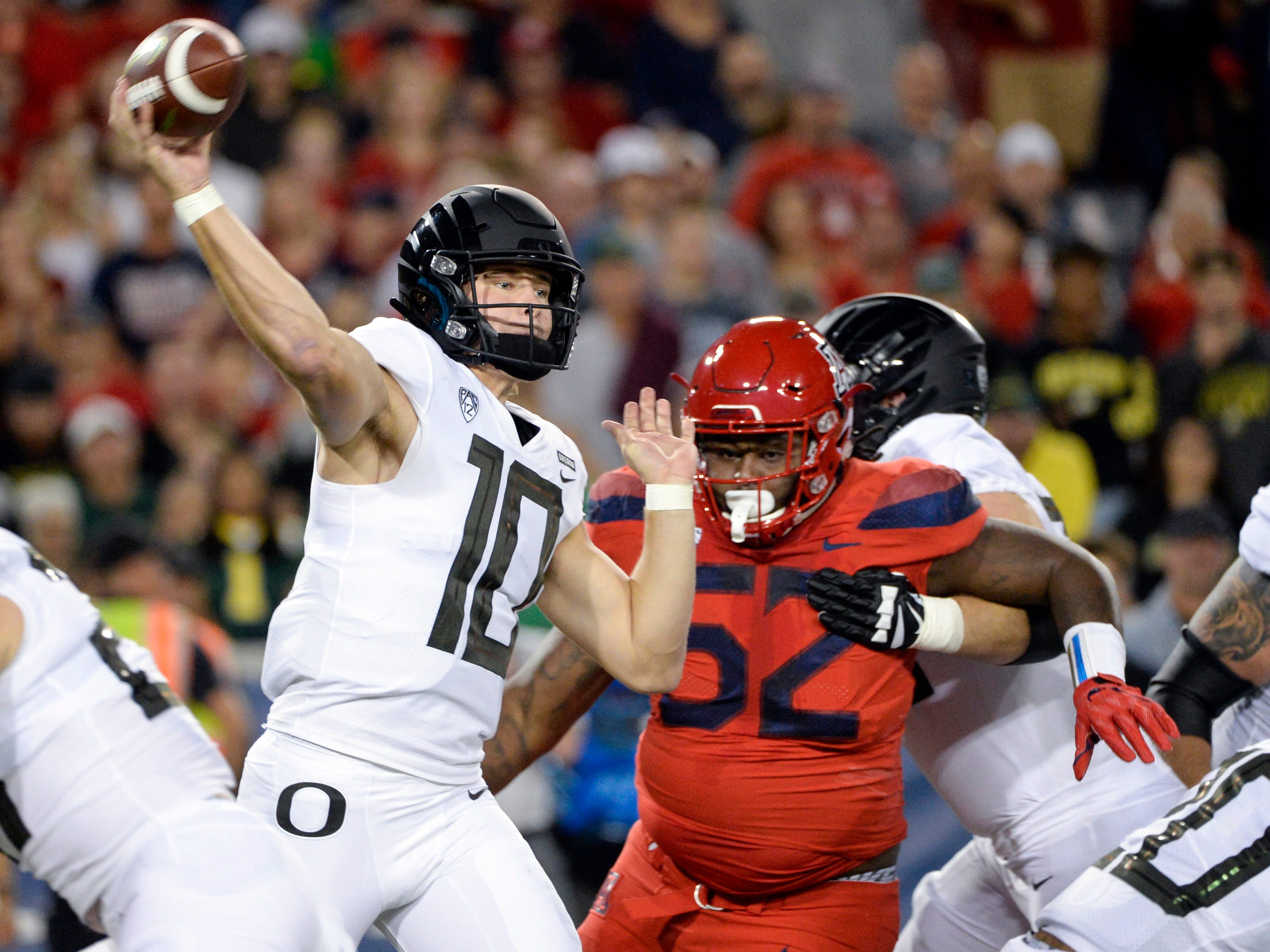 Oct 27, 2018; Tucson, AZ, USA; Oregon Ducks quarterback Justin Herbert (10) passes the ball under pressure from Arizona Wildcats defensive tackle PJ Johnson (52) during the first half at Arizona Stadium. Mandatory Credit: Casey Sapio-USA TODAY Sports
