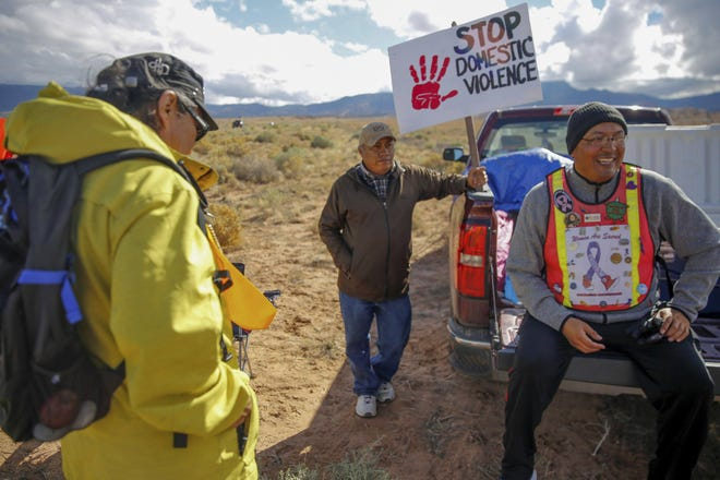 From left, Gary Mike, Jerald Begay and John Tsosie break for lunch along Navajo Route 13 in Red Valley, Ariz. on Oct. 18, 2018. The annual walk from Window Rock, Ariz., to Shiprock, N.M., is the ninth organized by a local father and son who aim to bring attention to social issues on the Navajo Nation through the event.