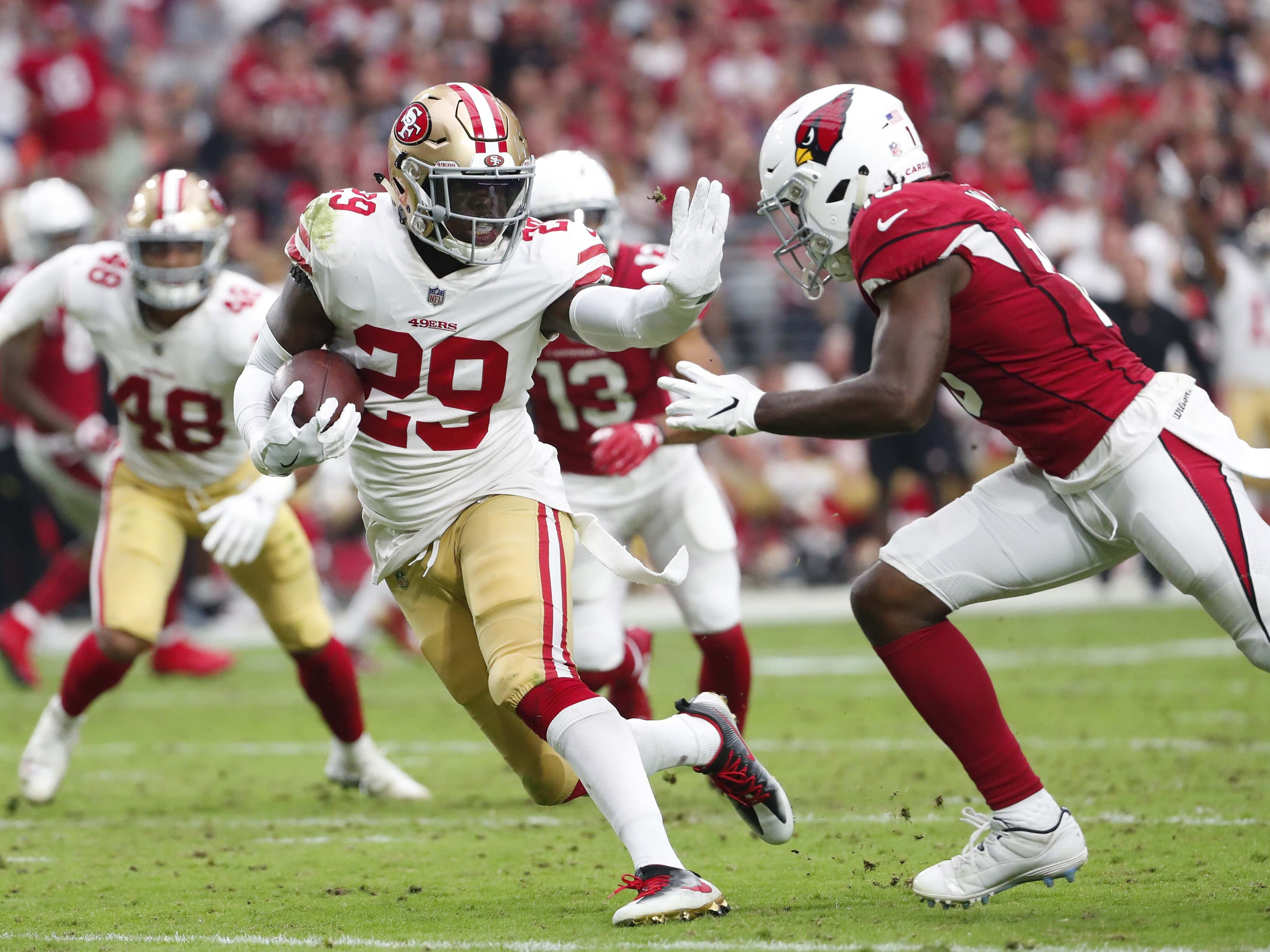 San Francisco 49ers strong safety Jaquiski Tartt (29) returns an interception against Arizona Cardinals wide receiver Chad Williams (10) In the second quarter during NFL action against the San Francisco 49ers on Oct. 28 at State Farm Stadium.