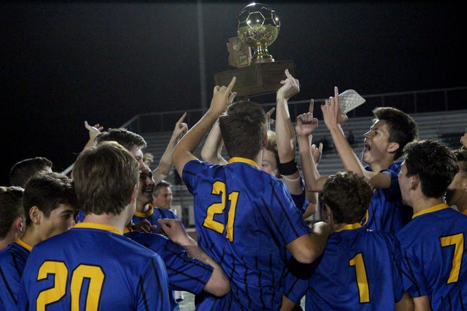 Phoenix Country Day celebrates with the 2A boys state championship trophy after beating Chino Valley's on Saturday at Campo Verde High School on Oct. 27.