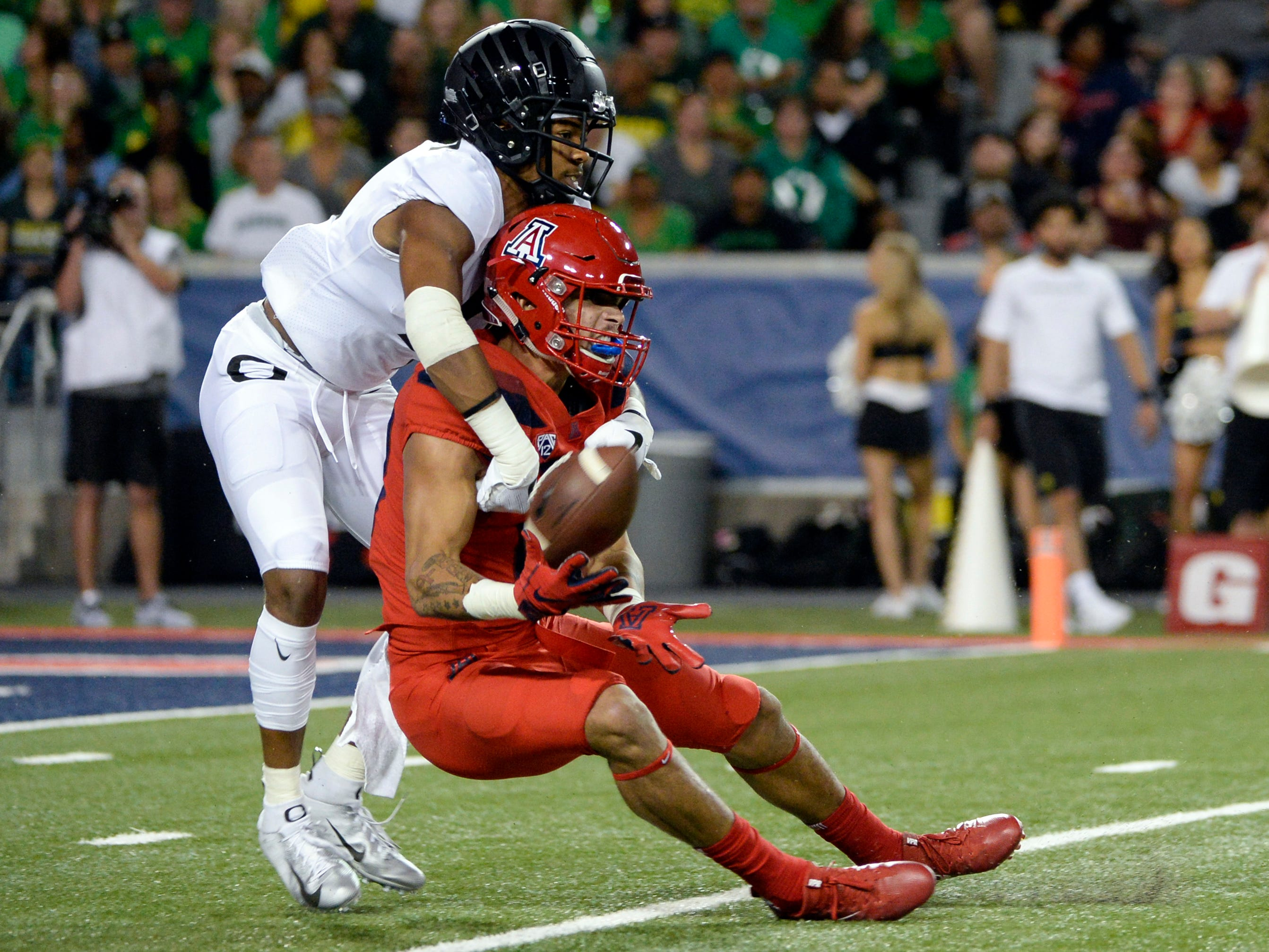Oct 27, 2018; Tucson, AZ, USA; Oregon Ducks cornerback Thomas Graham Jr. (4) and Arizona Wildcats wide receiver Shawn Poindexter (19) battle for the ball during the first half at Arizona Stadium. Mandatory Credit: Casey Sapio-USA TODAY Sports
