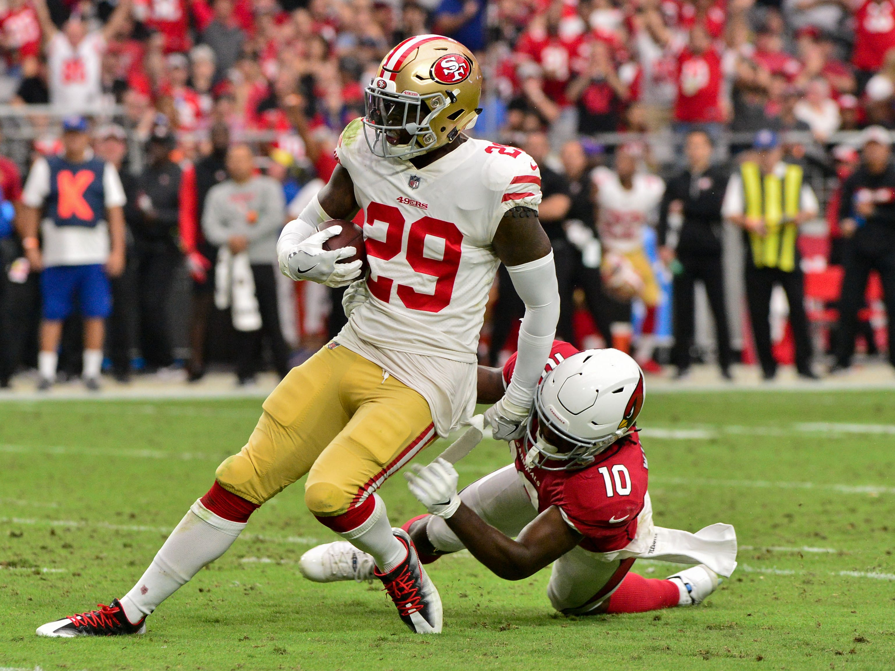 Oct 28, 2018; Glendale, AZ, USA; San Francisco 49ers safety Jaquiski Tartt (29) breaks a tackle from Arizona Cardinals wide receiver Chad Williams (10) while returning an interception during the first half at State Farm Stadium.