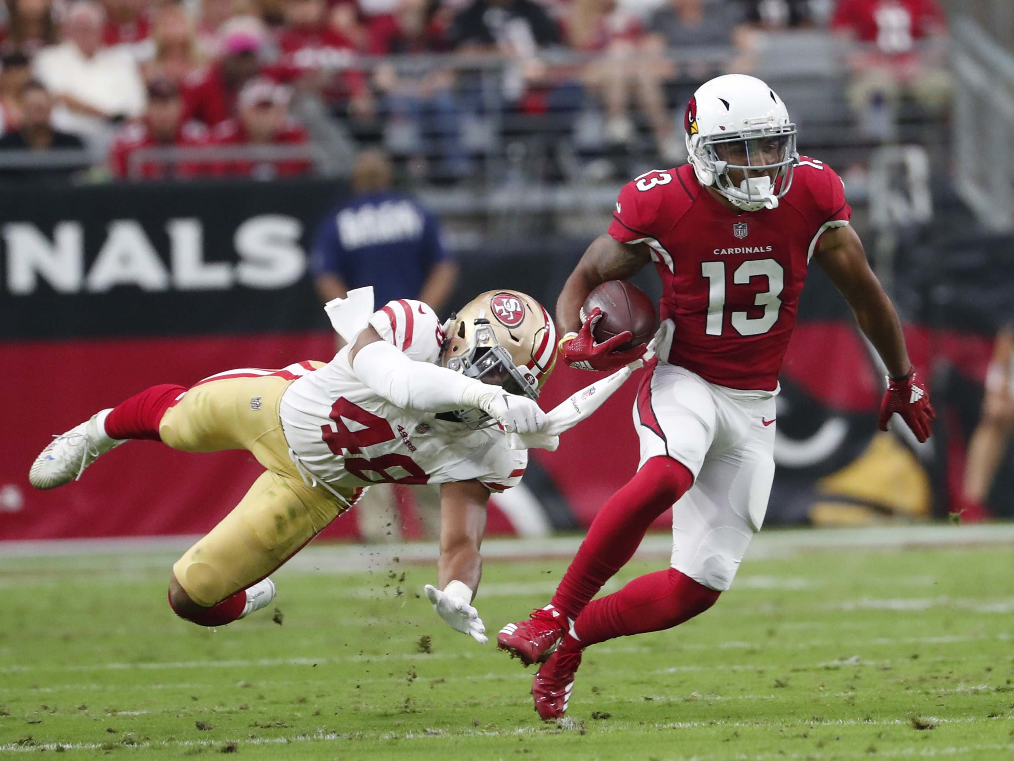 Arizona Cardinals wide receiver Christian Kirk (13)escapes a tackle by San Francisco 49ers linebacker Fred Warner (48) after a catch In the second quarter during NFL action against the San Francisco 49ers on Oct. 28 at State Farm Stadium.