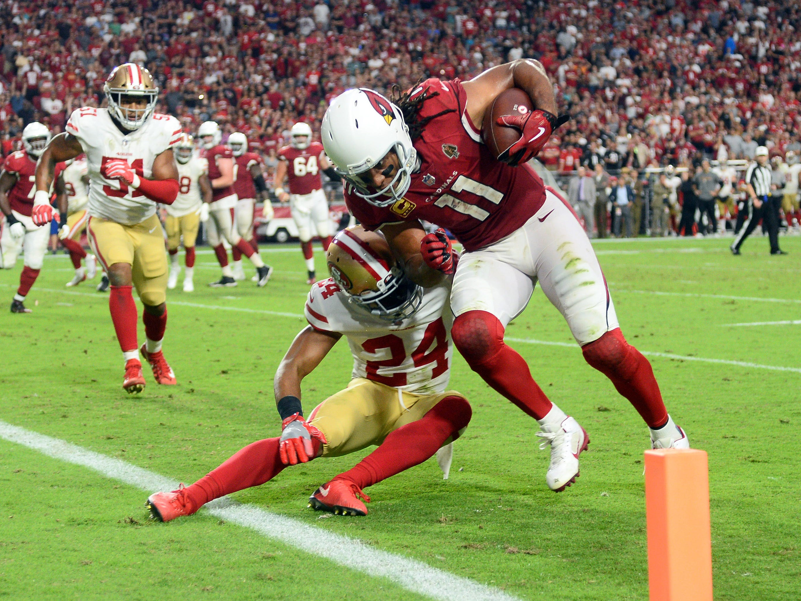 Oct 28, 2018; Glendale, AZ, USA; Arizona Cardinals wide receiver Larry Fitzgerald (11) breaks the tackle of San Francisco 49ers defensive back K'Waun Williams (24) to score a two point conversion during the second half at State Farm Stadium.