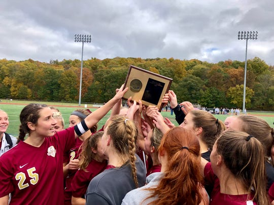 The Arlington girls soccer team celebrates with its championship plaque after winning a third straight Section 1 Class AA title on Sunday.