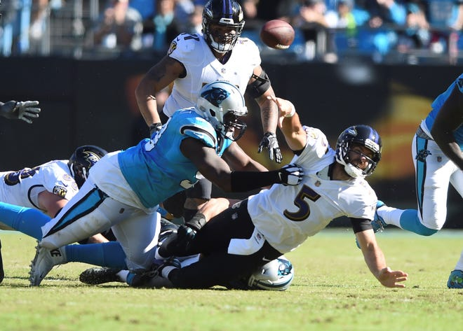 Baltimore Ravens' Joe Flacco (5) is sacked by Carolina Panthers' Kawann Short (99) and Luke Kuechly (59) in the second half of an NFL football game in Charlotte, N.C., Sunday, Oct. 28, 2018. (AP Photo/Mike McCarn)