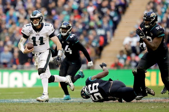 Philadelphia Eagles quarterback Carson Wentz (11)scrambles during the first half of an NFL football game against Jacksonville Jaguars at Wembley stadium in London, Sunday, Oct. 28, 2018. (AP Photo/Matt Dunham)