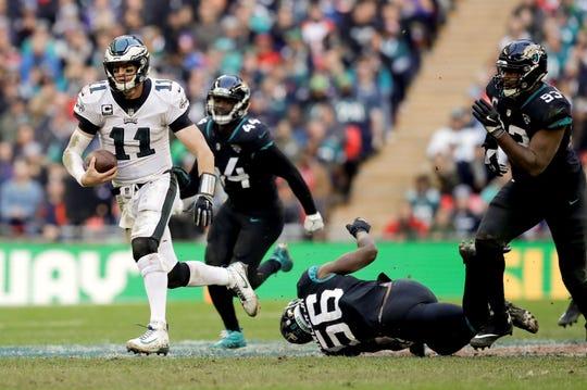 Philadelphia Eagles quarterback Carson Wentz (11)scrambles during the first half of an NFL football game against Jacksonville Jaguars at Wembley stadium in London, Sunday, Oct. 28, 2018. (AP Photo/Matt Dunham)