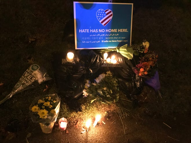 "In this photo from Saturday, people place flowers and candles beneath a sign that reads, ""Hate has no home here"" outside the Tree of Life Congregation Synagogue in Pittsburgh."