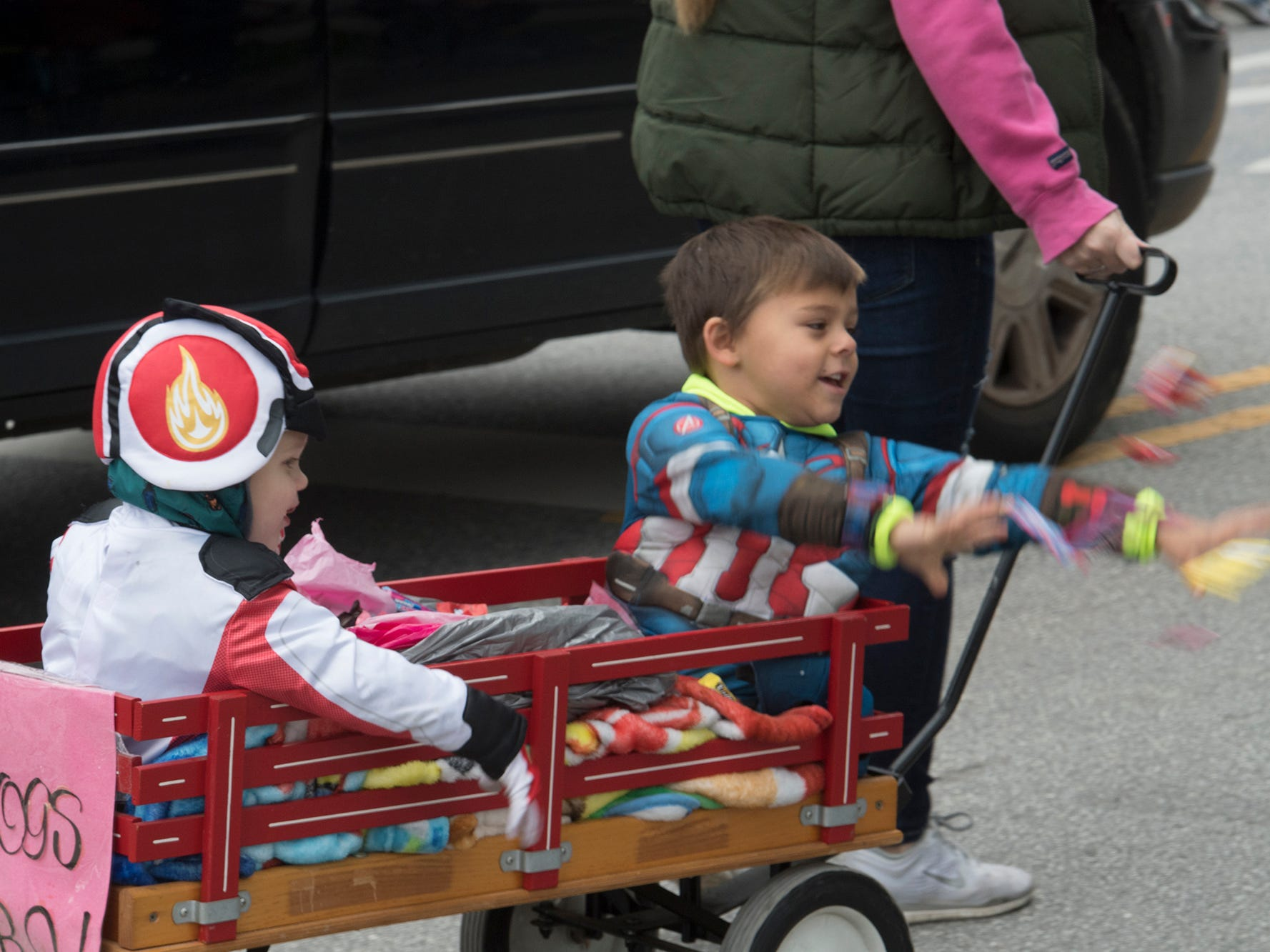 Children toss candy from a wagon during the 69th Annual York Halloween Parade presented by York Traditions Bank Sunday in York.