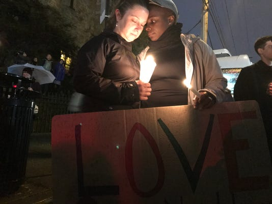 Amira Woodson, 39, left, and Alison Culyba, 39, attend a candle-light vigil in the Squirrel Hill neighborhood of Pittsburgh