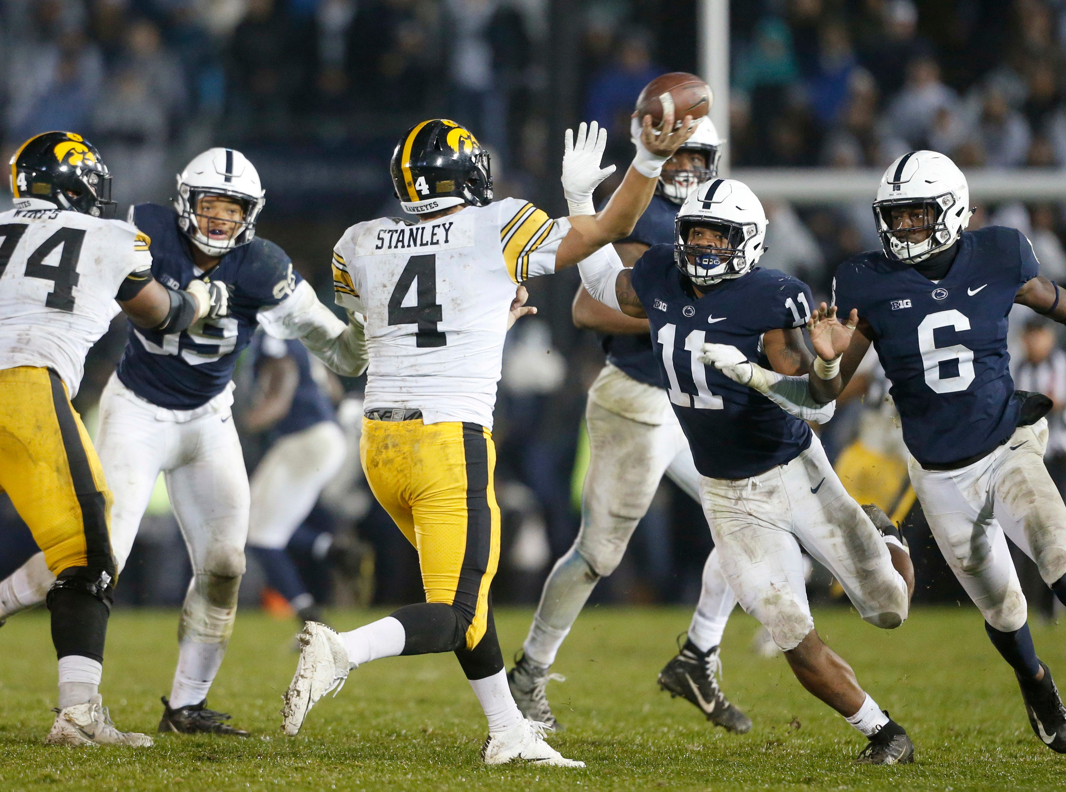 Iowa quarterback Nate Stanley (4) is pressured by Penn State's Micah Parson (11) and Cam Brown (6) as he throws during the second half of an NCAA college football game in State College, Pa., Saturday, Oct. 27, 2018. Penn State won 30-24. (AP Photo/Chris Knight)