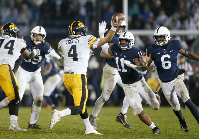 Iowa quarterback Nate Stanley (4) is pressured by Penn State's Micah Parsons (11) and Cam Brown (6) as he throws during the second half of an NCAA college football game in State College, Pa., Saturday, Oct. 27, 2018. Penn State won 30-24. (AP Photo/Chris Knight)