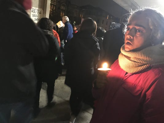 "Sukanya Srinivasan, 46, watches as hundreds gather during a vigil outside the Jewish Community Center. A Squirrel Hill resident since 1997. ""Squirrel Hill is so inclusive, you'd never imagine something like this to ever happen here,"" said Srinivasan."