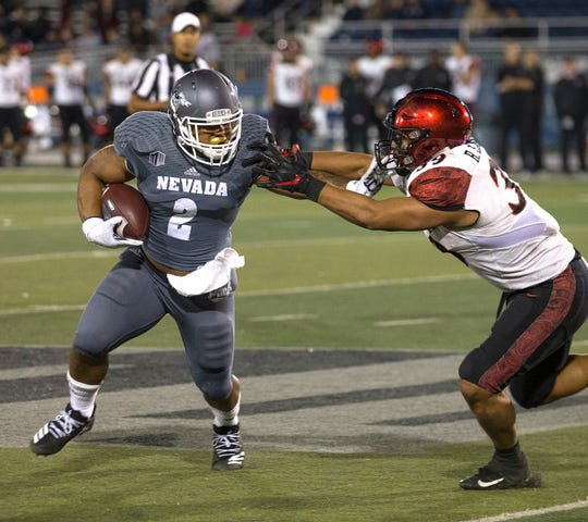 Nevada running back Devonte Lee (2) straight-arms San Diego State's Ronley Lakalaka during the Wolf Pack's win over the Aztecs on Saturday.