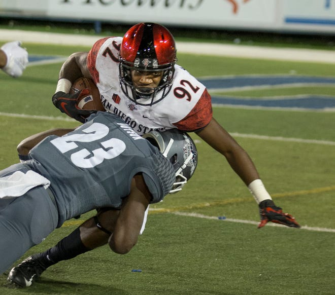 San Diego State's Kobe Smith (92) is hit by Nevada's Jomon Dotson during the second half of Saturday's game at Mackay Stadium.