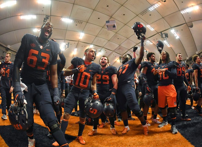 Syracuse players celebrate after defeating North Carolina State 51-41 at the Carrier Dome on Saturday night.