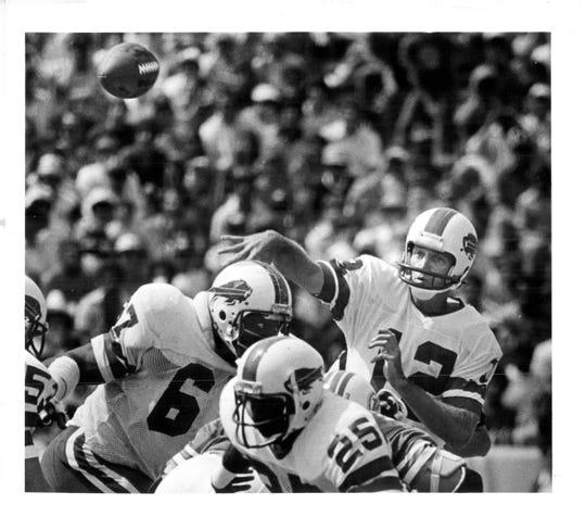 Buffalo Bills quarterback Joe Ferguson gets off a pass thanks to good blocking Reggie McKenzie (67) and Roland Hooks (25) in 1980.