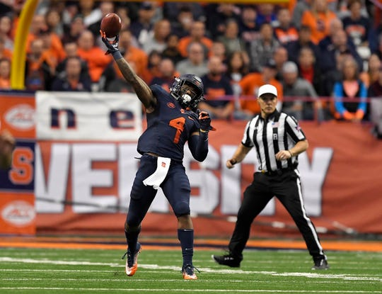 Syracuse running back Dontae Strickland (4) throws a pass to wide receiver Jamal Custis during the first half of Saturday's game against North Carolina State.