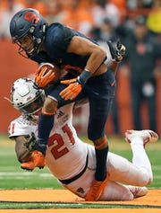 Syracuse wide receiver Sean Riley, top, tries to break the grasp of North Carolina State defensive back Stephen Griffin after a reception during the second half on Saturday night.