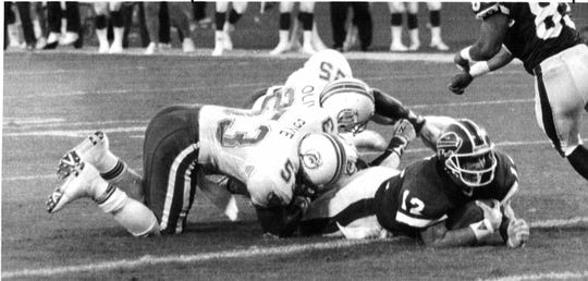 Buffalo Bills quarterback Jim Kelly sneaks into the endzone to score the winning touchdown against the Miami Dolphins during the 1989 regular season opener game for the two teams.