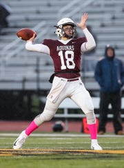 Aquinas quarterback Tyler Szalkowski (18) throws a long ball during a Section V Class AA semifinal game against Pittsford at The College at Brockport. Aquinas won 27-3.