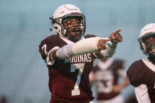 Aquinas running back Caron Robinson (7) celebrates his first touchdown of the day against Pittsford during a Section V Class AA semifinal high school football game at The College at Brockport.