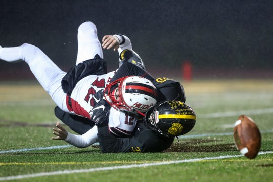 October 27, 2018; Brockport, NY; USA; McQuaid defensive end Connor Zamiara (30) sacks and forces Hilton quarterback Ryan Butts (12) to fumble during a Section V Class AA semifinal high school football game at Brockport College.  Photo: Christopher Cecere