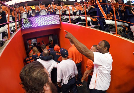 Syracuse head coach Dino Babers, right, acknowledges fans on his way to the locker room after the team's 51-41 win over North Carolina State on Saturday night.