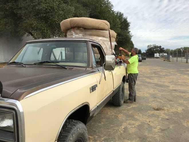 Travis Clements of Shasta ties down a load of straw wattles Sunday that he picked up for free from the city of Redding and McConnell Foundation.