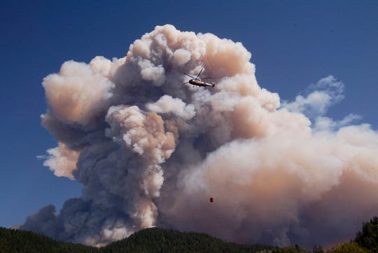 FILE - In this Aug. 17, 2002, file photo, a Sikorsky 61 helicopter prepares to refuel in Agness, Ore., as a column of smoke rises from the Biscuit Fire. A Portland, Ore., couple has spent years clearing the wild and remote Trans-Kalmiopsis Trail with hand tools after the raging wildfire destroyed much of it in 2002. (AP Photo/John Gress, File)