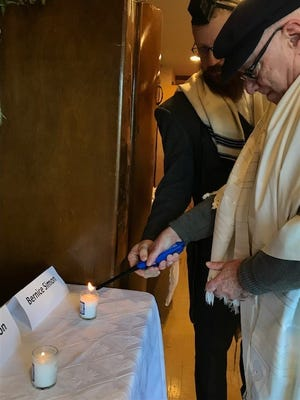 Rabbi Avrohom Perlstein and a congregant light candles for those slain in Saturday's attack at a Pittsburgh synagogue.