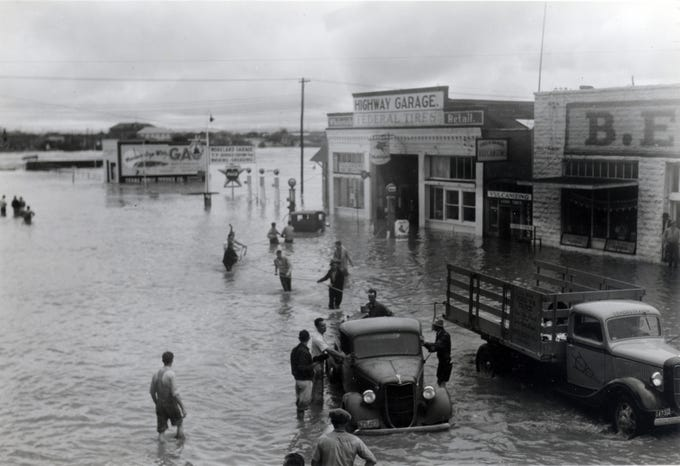 People try to help pull a stalled vehicle during the San Angelo flood of 1936.