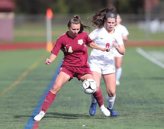 Arlington's Kate Murphy (14) and North Rockland's Megan MacMillan (6) battle for possession during the girls Class AA soccer sectional title at Arlington High School in Freedon Plains on Sunday, October 28, 2018.