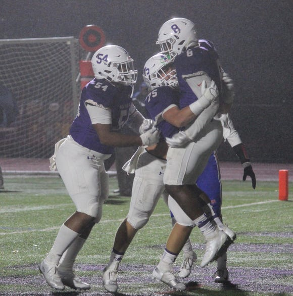 New Rochelle's Jordan Forrest (8) celebrates with teammates Vinny Ruggiero (75) and Jaheim Jones (54) after scoring a touchdown. The Huguenots beat Carmel 54-34 in a Section 1 Class AA semifinal at New Rochelle High School Oct. 27, 2018.