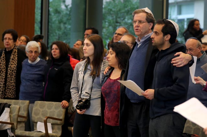 "David Harris of Chappaqua, second from right, CEO of the American Jewish Committee, sings ""We Shall Overcome"" along with others at the end of a vigil at Congregation Kol Ami in White Plains Oct. 28, 2018. Over one-thousand people attended the vigil in response to Saturday's fatal shooting at a Pittsburgh synagogue. The gathering was organized by several Westchester County based Jewish organizations ."