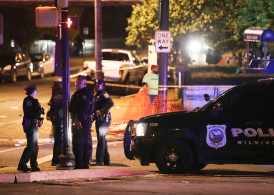 Wilmington police and other officers keep the peace after reports of gunfire and fighting at Kelly's Logan House in Trolley Square at the conclusion of the city's Halloween Loop early Sunday.