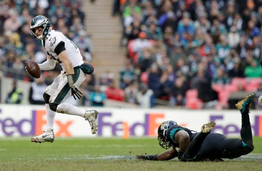 Philadelphia Eagles quarterback Carson Wentz (11), left, skips out of a tackle during the second half of an NFL football game against Jacksonville Jaguars at Wembley stadium in London, Sunday, Oct. 28, 2018. (AP Photo/Matt Dunham)
