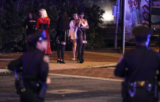 Costumed participants linger along Delaware Avenue as Wilmington police and other officers keep the peace after reports of gunfire and fighting at Kelly's Logan House in Trolley Square at the conclusion of the city's Halloween Loop early Sunday.
