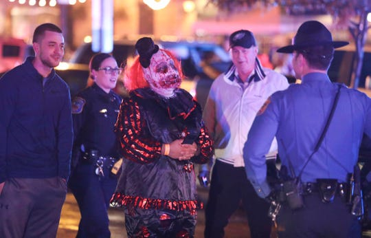 A costumed Halloween Loop participant speaks to police after a gun was fired  at Kelly's Logan House in Wilmington during Halloween Loop. No one was injured.